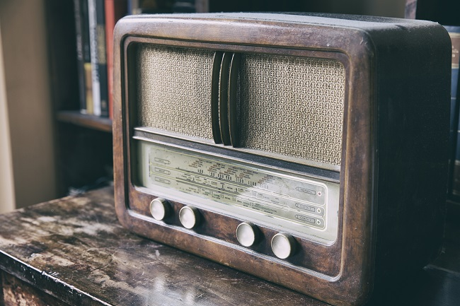 Old-fashioned wooden radio sitting on cabinet